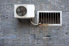 Ett fönster och en luftkonditioneringsapparat på den gråa texturen för bakgrund för tegelstenvägg Royaltyfri Fotografi