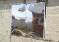 Ett fönster som göras av plexiglas i en betongvägg Ett fönster med en reflekterande klistermärke Royaltyfri Fotografi
