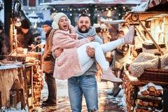 Ett förälskat attraktivt par En stilig man som tillsammans rymmer hans flickvän på händer och att ha gyckel, medan stå på arkivbild