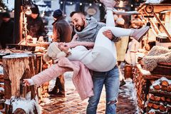 Ett förälskat attraktivt par En stilig man som tillsammans rymmer hans flickvän på händer och att ha gyckel, medan stå på royaltyfri fotografi