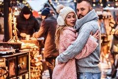 Ett förälskat charmigt par och att krama tillsammans och se en kamera, medan stå på julmässan arkivbilder