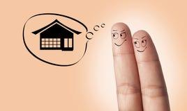 Ett förälskat fingerpar och hus Arkivfoton