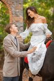 Ett förälskat par för ung nedgång på ett utomhus- datum Kvinnan och mannen med hästen som går i höst, parkerar fotografering för bildbyråer