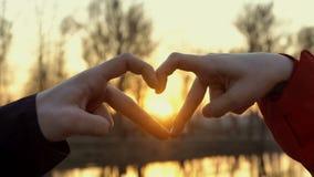 Ett förälskat par förbinder deras händer i formen av en hjärta mot en ljus gul solnedgång Se solen igenom lager videofilmer