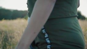 Ett förälskat ungt par, en grabb och en flicka, rymmer händer och att gå över fältet i soligt sommarväder stock video