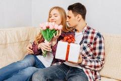 Ett förälskat ungt par, en man gratulerar en kvinna, genom att ge henne en bukett av tulpan och en gåva som hemma sitter på soffa royaltyfri foto