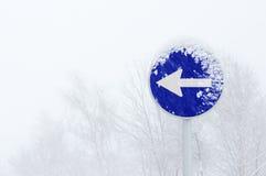 Ett för riktningstrafik för väg obligatoriskt tecken med häftiga snöstormen Arkivbilder