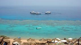 Ett förbluffa klart Röda havet med korallrever Fartyg paraplyer, solsängar Farsha strand Sharm El Sheikh, Egypten Arkivbild