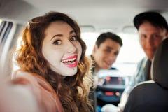Ett företag av fyra vänner gör selfie inom bilen arkivfoton