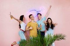 Ett företag av snygga vänner som skrattar som dricker gula coctailar, står framme av den rosa väggen och bak royaltyfria foton