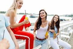 Ett företag av snygga vänner som skrattar och dricker gula coctailar i det trevliga kafét bredvid floden fotografering för bildbyråer
