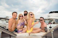 Ett företag av unga vänner som dricker champagne på aktern av a royaltyfri fotografi