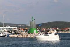 Ett företag av vänner på en liten motoryacht skriver in marina som seglar förbi en stenvågbrytare med en våldsam signalfyr rest fotografering för bildbyråer