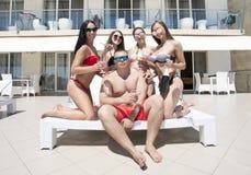 Ett företag av vänner på en semesterortbakgrund Le kvinnor i bikinier och en manlig grabb Sommarparti Lyxig semester royaltyfria foton