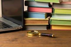 Ett förstoringsglas, en bunt av böcker och en bärbar dator på en trätabell Begreppet av informationssökandet på internet och böck arkivfoto