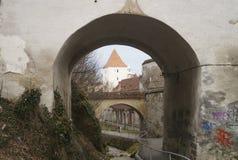 Ett försvartorn som igenom ses en av de välvda portarna av knegbastionen, Rumänien, Brasov Bastionul kneg 1515 - 1 royaltyfri fotografi