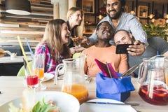 Ett f?retag av m?ngkulturella ungdomari ett kaf? som ?ter pizza och att dricka coctailar och att ha gyckel fotografering för bildbyråer