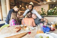 Ett f?retag av m?ngkulturella ungdomari ett kaf? som ?ter pizza och att dricka coctailar och att ha gyckel arkivbilder