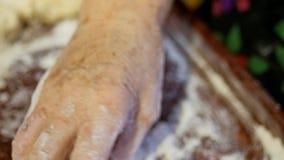 Ett familjrecept, händer för mormor` s knådar degen för bullar lager videofilmer