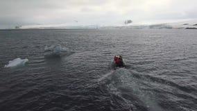 Ett fartyg med folk som svävar runt om stycken av ett isberg Andreev arkivfilmer