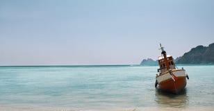 Ett fartyg sitter anslutit på en tropisk ö Arkivbild