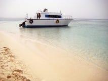 Ett fartyg som förtöjas till en öde sandig strand Royaltyfri Foto