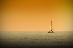 Ett fartyg som navigerar ett tranquile hav på solnedgångtid Mörker - orange atmosfär Royaltyfri Bild