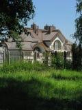 Ett fast hus bak ett järnstaket med ett staket med en liten balkong med ett växande grönt gräs nära staketet Royaltyfri Bild