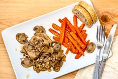 Ett fegt kött, skivade morötter, champinjoner och ett bröd royaltyfria foton