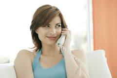 ett felanmälan som gör den le kvinnan för telefon Arkivfoto