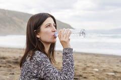Ett flickadricksvatten i stranden arkivfoto
