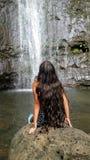 Ett flickasammanträde på det stort vaggar belägen mitt emot vattenfall Arkivbild