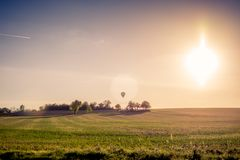 Ett flyg för ballong för varm luft över fältet på solnedgången royaltyfria foton