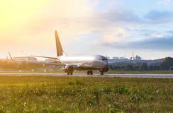 Ett flyg för silverpassagerarenivå i den färgrika himlen Flygplan tar av från flygplatslandningsbanan under solnedgången Royaltyfri Foto