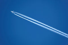Flygplan med contrailen Arkivfoton