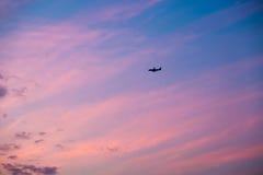 Ett flygplanflyg på skymning Arkivbild
