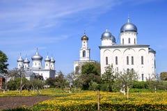 Ett forntida högt vitt klockatorn och en kyrka i en kloster Royaltyfri Foto