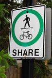 Ett fot- tecken för cyklistaktiebana som har vandaliserats för att visa en skateboarder i stället Royaltyfria Bilder