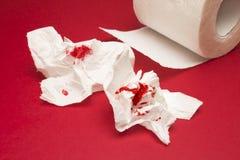 Ett foto av använt skiter av blodigt toalettpapper och en rulle för toalettpapper på den röda bakgrunden Menstruations- blöda för royaltyfria foton