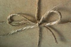 Ett foto av en fnuren med en pilbåge av tvinnar bundet över kraft papper på asken royaltyfri bild