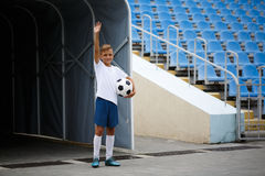 Ett foto av en sportig unge med en fotbollboll på en stadionbakgrund Utomhus aktiviteter Barn som utbildar fotboll Arkivfoto