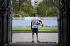 Ett foto av en sportig unge med en fotbollboll på en stadionbakgrund Utomhus aktiviteter Barn som utbildar fotboll Arkivbilder
