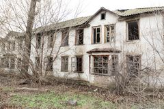 Ett foto av ett gammalt och ruskigt övergett lantbrukarhem, som försämras som slutligen är bevuxet med gamla träd Bodde här ett g Royaltyfri Bild