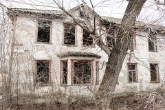 Ett foto av ett gammalt och ruskigt övergett lantbrukarhem, som försämras som slutligen är bevuxet med gamla träd Bodde här ett g Arkivbild
