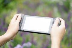 Ett foto av 2 händer som rymmer Nintendo Swtich, medan spela den anonyma leken i trädgården arkivfoto