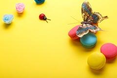 Ett foto av olika makron och en fjäril, rosor, nyckelpiga skjutit från över, på en gul bakgrund med ett ställe för text arkivfoto