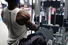 Ett foto från baksidan av en svart muskulös man i en vit T-tröja som är förlovad i en simulator fotografering för bildbyråer