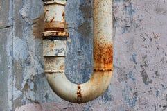 Ett fragment av det gamla rostiga vattenröret på sjaskig väggbakgrund Royaltyfri Fotografi