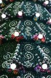 Ett fragment av en enorm julgran med många prydnader, gåvaaskar och lysande lampor Foto av en dekorerad julgranclose- vektor illustrationer