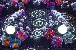 Ett fragment av en enorm julgran med många prydnader, gåvaaskar och lysande lampor Foto av en dekorerad julgranclose- royaltyfri illustrationer